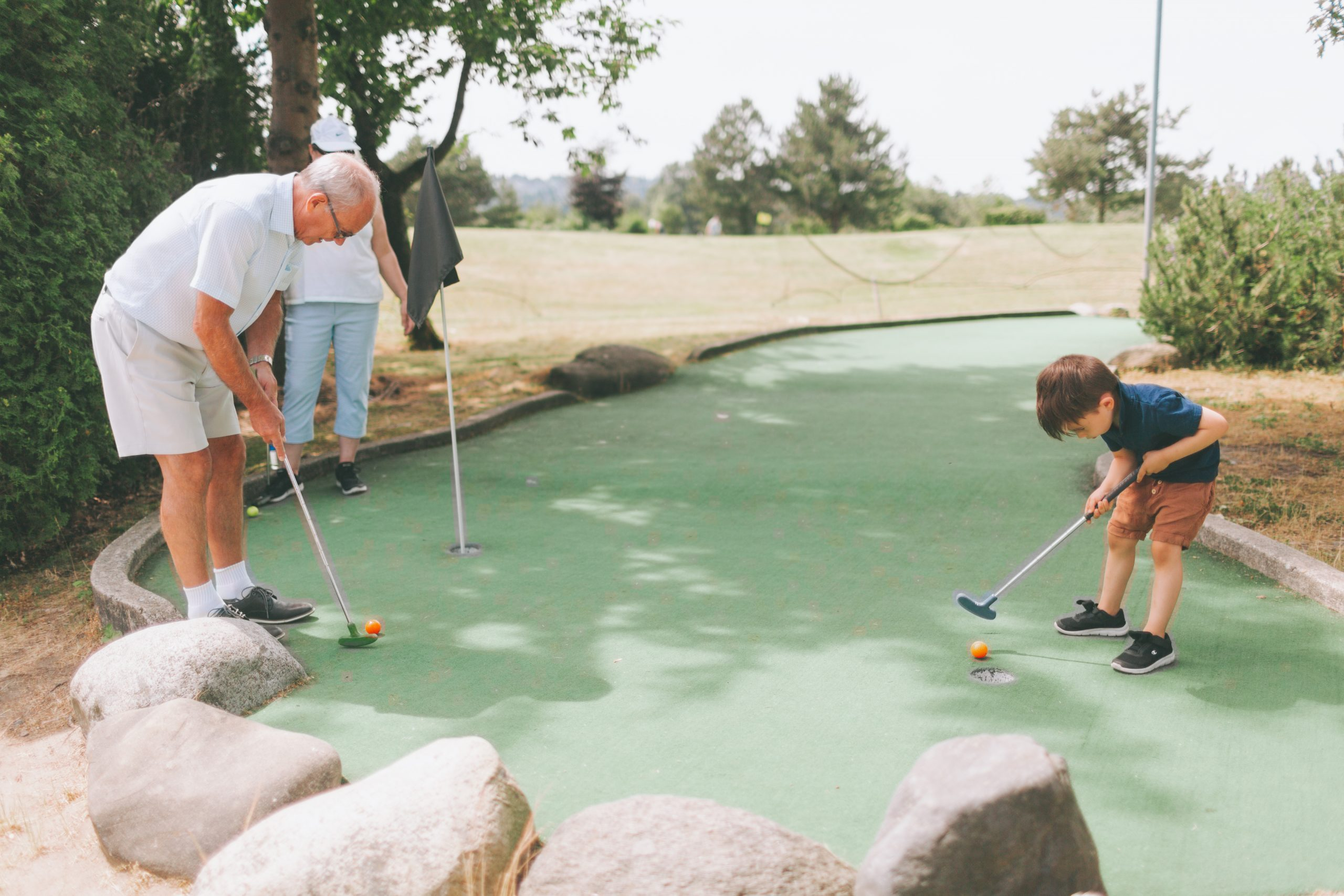 a-grandfather-and-his-grandson-playing-mini-golf
